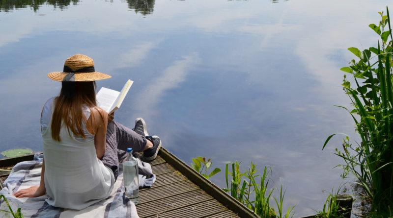Woman reading a book, lake.